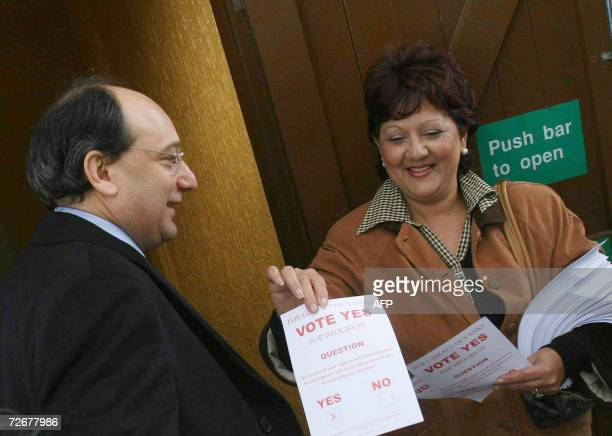 A woman from the 'Yes' camp hands a leaflet to Minister of Gibralter Peter Caruana as he arrives to vote in a referendum set to enshrine a new...