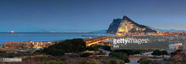 gibraltar rock and la linea de la conception at blue hour - morocco (africa) in the background (spain and gibraltar/ uk) - ジブラルタルの岩山 ストックフォトと画像