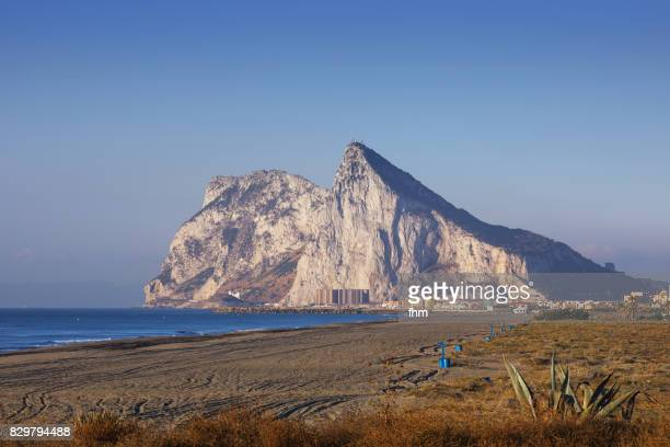 gibraltar rock and the beach of linea de la conception at blue hour - morocco (africa) in the background (spain and gibraltar/ uk) - rock of gibraltar stock photos and pictures