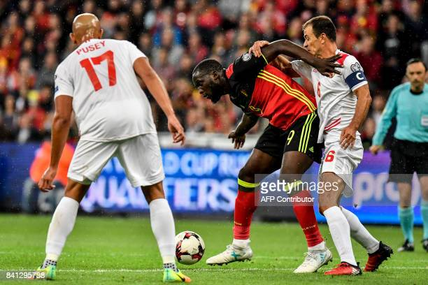 Gibraltar's Jason Pusey, Belgium's Romelu Lukaku and Gibraltar's Roy Chipolina vie for the ball during the WC 2018 football qualification football...