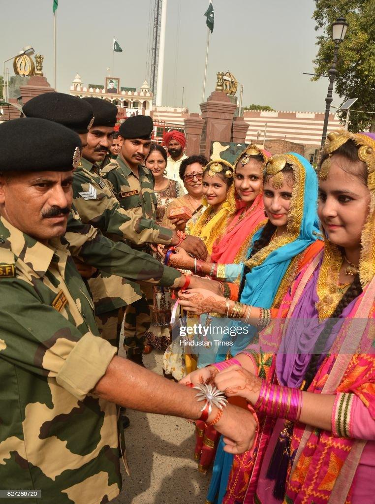Giddha girls tying rakhi on the wrists of Border Security Force Jawans on the occasion of Raksha Bandhan festival at Attar Border near on August 7...