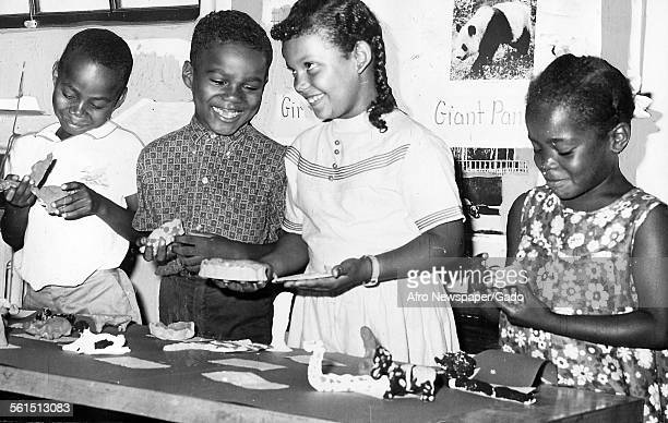 Gidding School open house and pupils, boys and girls, looking at the clay models they have made, Baltimore, Maryland, August 9, 1967.