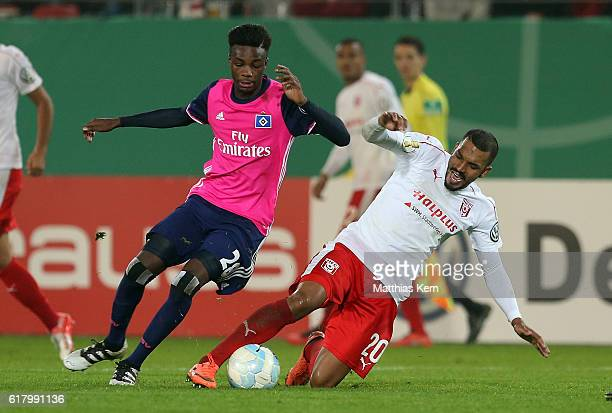 Gideon Jung of Hamburg battles for the ball with Royal Dominique Fennell of Halle during the DFB Cup second round match between Hallescher FC and...