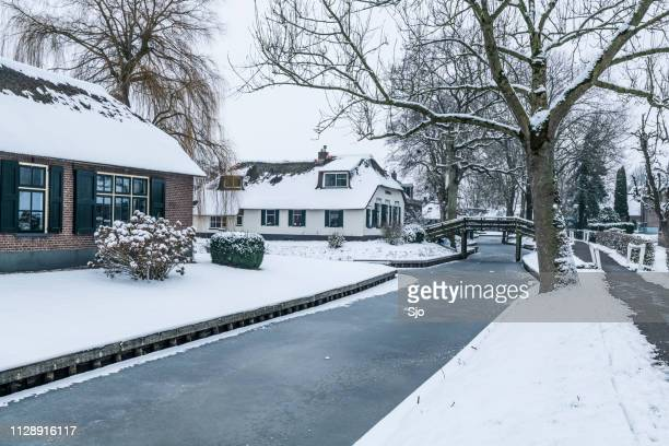 giethoorn village with the canals with snow during a cold but beautiful calm winter day - giethoorn stock pictures, royalty-free photos & images