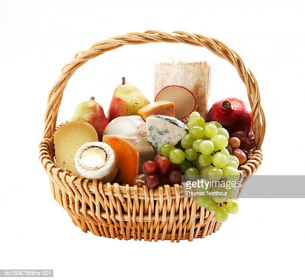 Gift basket of fruit and cheese on white background