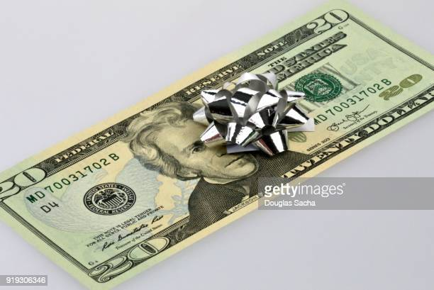 Gift bow decorating a gift of US cash