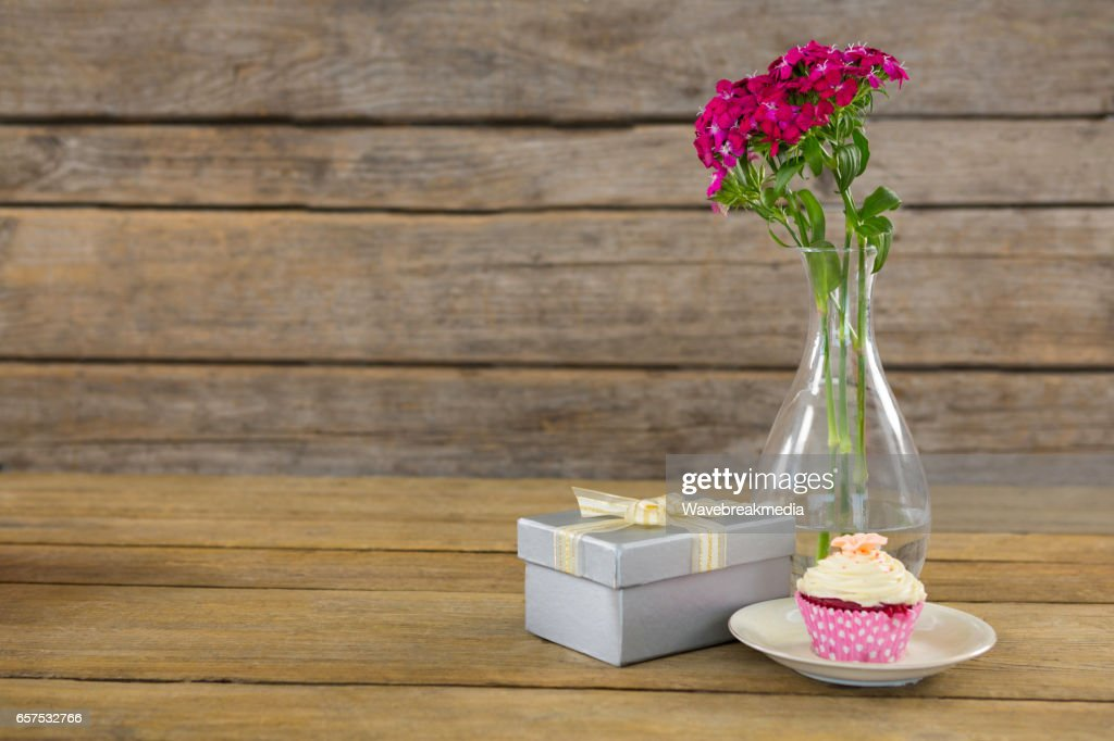 Getty Images & Gift Box And Flower Vase With Cupcake In Plate On Wooden ...