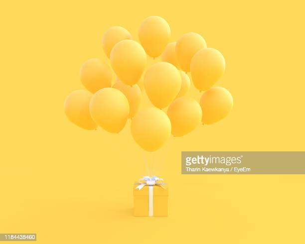 gift box with balloons against yellow background - jaune photos et images de collection