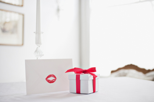 Gift box with ribbon and card with lipstick kiss on desk - gettyimageskorea