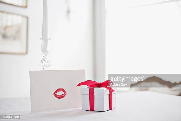 gift box with ribbon and card with lipstick kiss on desk - valentine's day stock pictures, royalty-free photos & images
