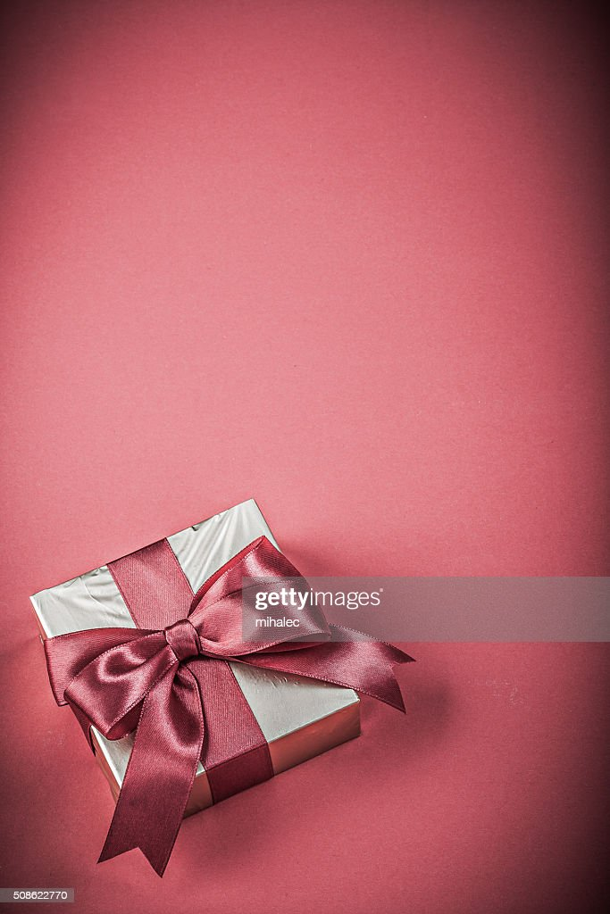 Gift box with tied ribbon on red background holidays concept : Stock Photo