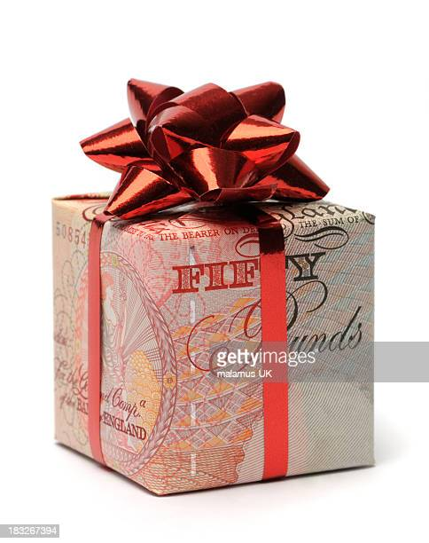 gift box wrapped in an english pound with a red bow - british pound sterling note stock pictures, royalty-free photos & images