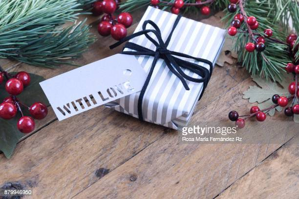 Gift box wrapped in gray and black striped paper and greeting card with the words 'with love' written on wooden background. Selective focus and copy space.