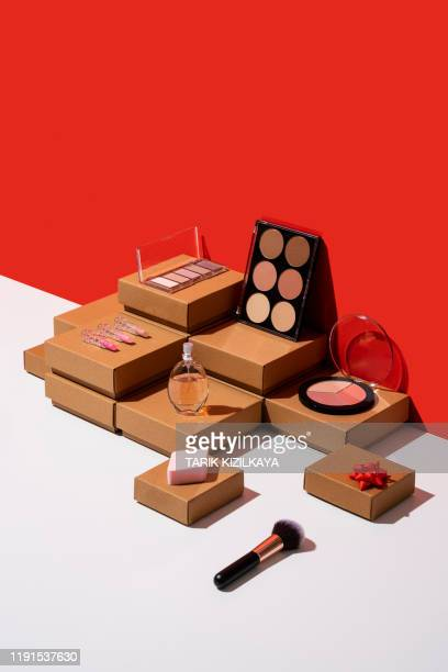 gift boxes and makeup accessories organized neatly on red and white background - make up stock pictures, royalty-free photos & images
