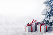 Gift boxes in snow under tree