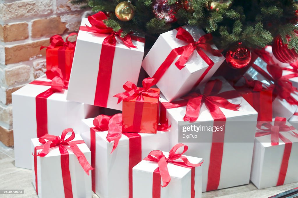 Gift boxes piled under Christmas tree : Stock Photo