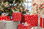 Gift boxes under Christmas tree, New Year home decorations, red wrapping Santa presents, fir tree decorated, beautiful bokeh of garland.