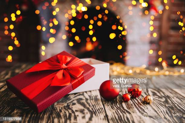 gift boxes with a large red bow  against a background bokeh of twinkling party lights. luxury new year gift. christmas gift. christmas background with gift box. christmastime celebration - ribbon sewing item stock pictures, royalty-free photos & images