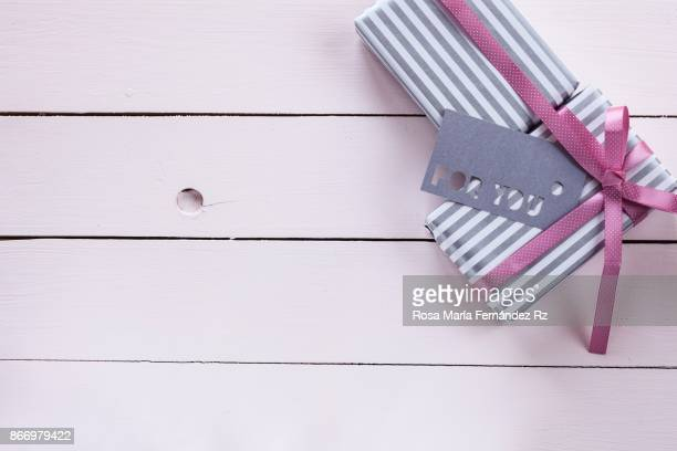 Gift boxes wrapped in striped paper, pink ribbon and labbel on wooden background painted in pink. Top View and copy space.
