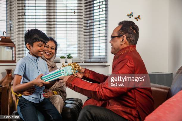 gift giving with his grandfather - hari raya celebration stock pictures, royalty-free photos & images