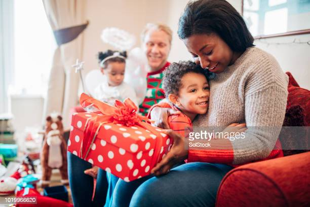gift giving with his mother at christmas time - gift stock pictures, royalty-free photos & images