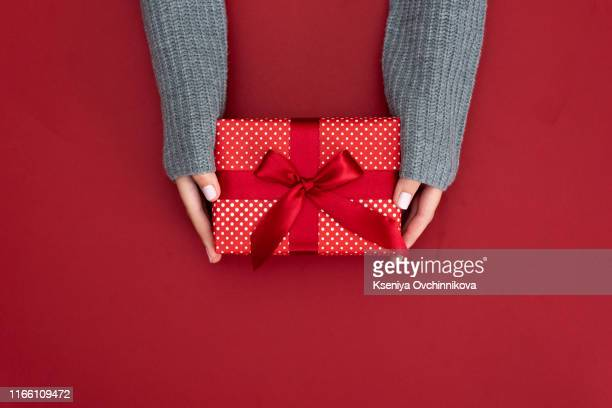 gift in female hands on a colored background top view. - 贈り物 ストックフォトと画像