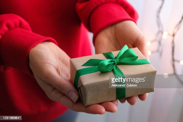 a gift in the hands of a woman, tied with a bright green ribbon, against the background of golden twinkling fairy lights of a garland. a girl in a red sweater gives or receives a gift on the eve of a holiday. the concept of a happy christmas. - 西シベリア ストックフォトと画像