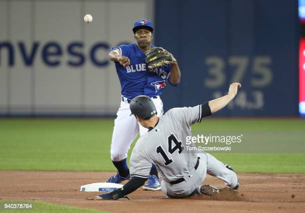 Gift Ngoepe of the Toronto Blue Jays turns a double play in the first inning during MLB game action as Neil Walker of the New York Yankees slides...