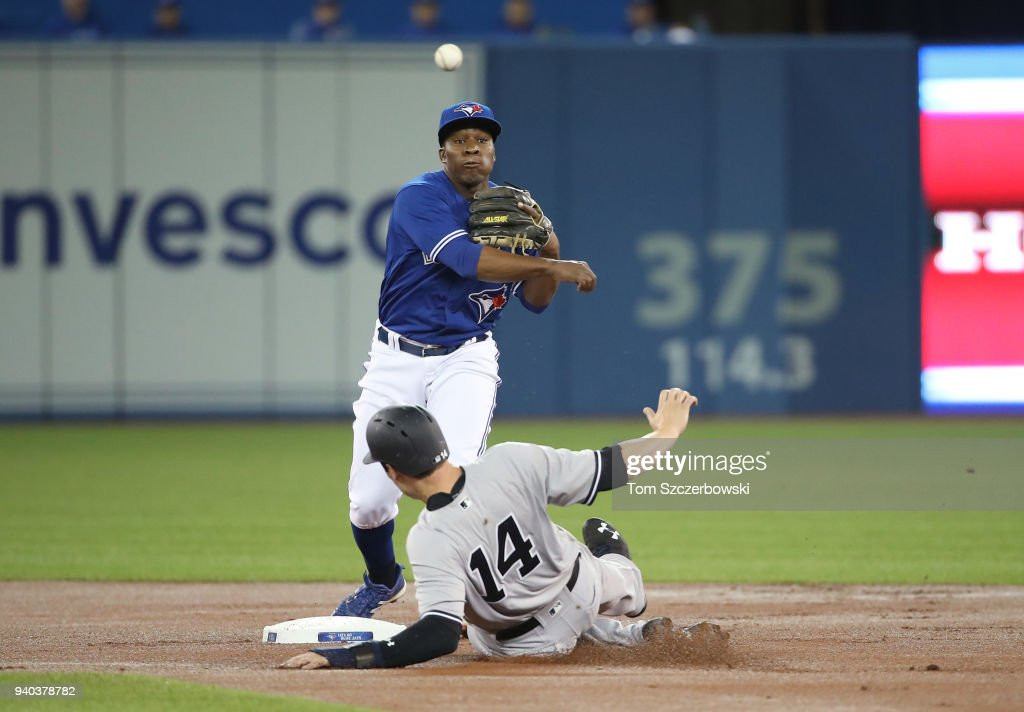 Gift Ngoepe #61 of the Toronto Blue Jays turns a double play in the first inning during MLB game action as Neil Walker #14 of the New York Yankees slides into second base at Rogers Centre on March 31, 2018 in Toronto, Canada.