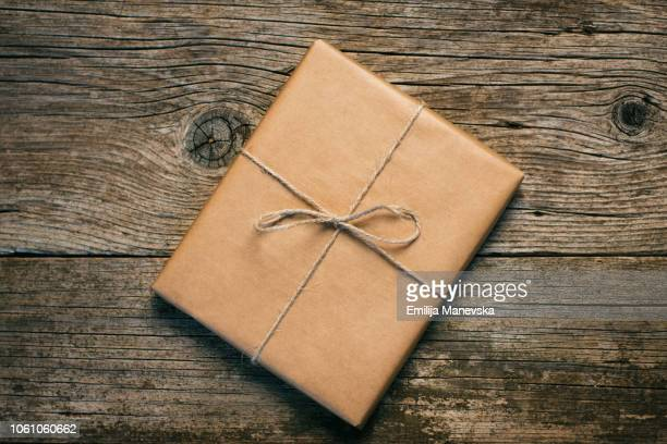 gift on wooden table - brown stock pictures, royalty-free photos & images