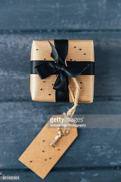 Gift romantic box with black bow on wood background