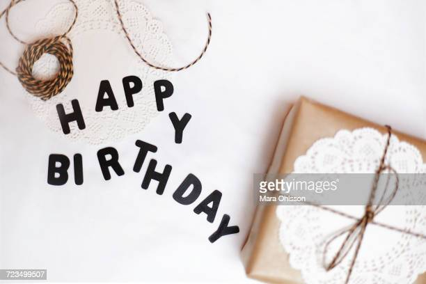 Gift wrapped in brown paper, doily and string, beside letters spelling Happy Birthday