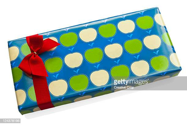 A gift wrapped in paper and a red bow ribbon