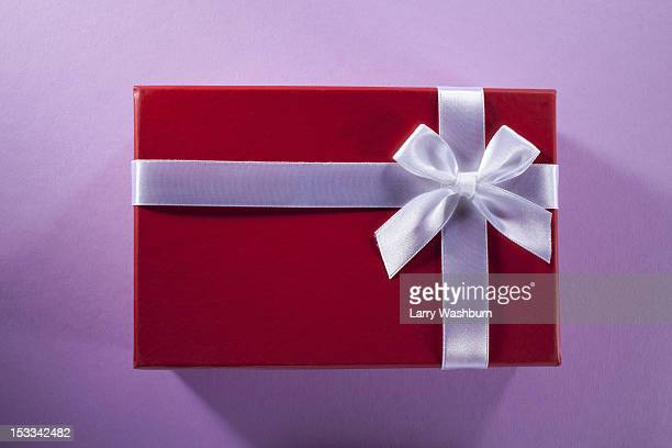 A gift wrapped in red paper and white ribbon and bow