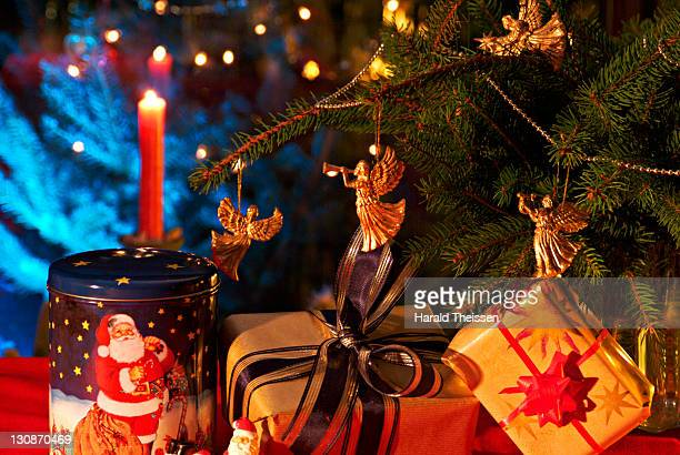 Gifts and burning candles in front of a lit Christmas tree