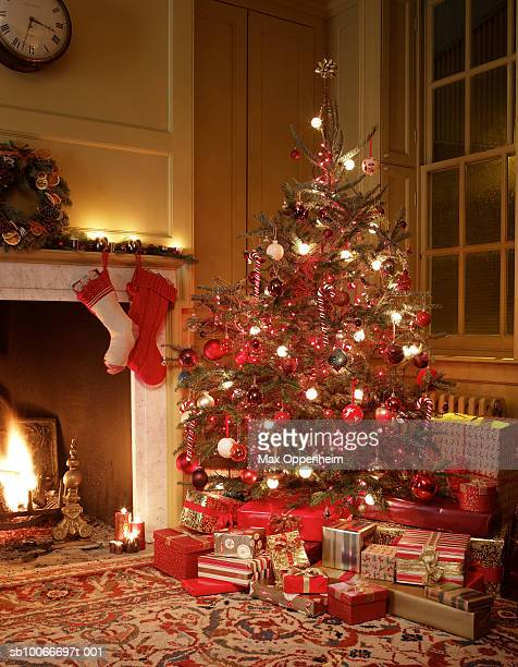 gifts in front of christmas tree - christmas stocking stock pictures, royalty-free photos & images