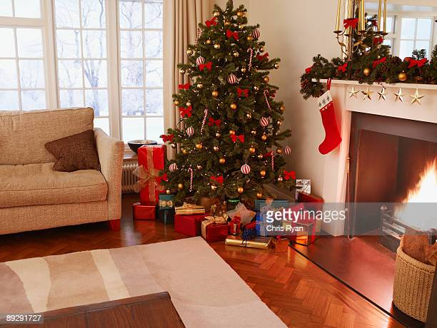 gifts under christmas tree in living room - tradition stock pictures, royalty-free photos & images