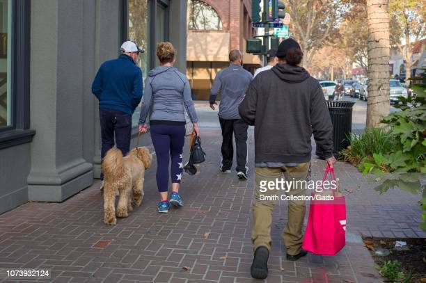 Gig economy worker walks down University Avenue in the Silicon Valley town of Palo Alto, California, carrying the distinctive red bag of food...