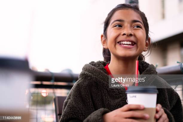 giggling pre-adolescent girl holding cup - pre season bildbanksfoton och bilder