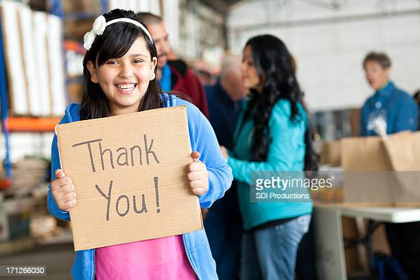 Giggling young girl holding Thank You sign at donation center