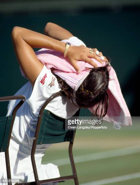 Gigi Fernandez of the USA taking a break during a women's singles match at the Wimbledon Lawn Tennis Championships in London, circa July, 1994. The...