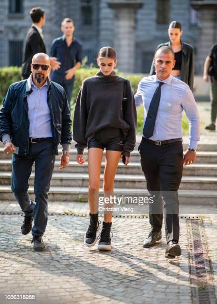 Gigi Hadid wearing black turtleneck knit white navy cropped denim jeans white sneakers is seen outside Max Mara during Milan Fashion Week...