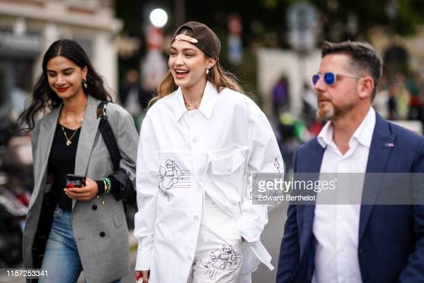 Gigi Hadid wears a brown cap earrings necklaces a white shirt with cartoon drawings pattern assorted pants outside Vuitton during Paris Fashion Week...