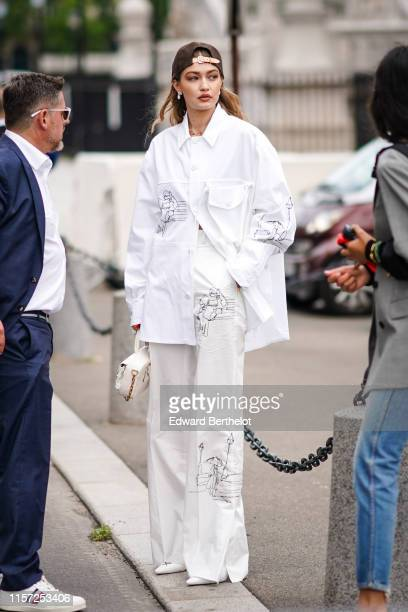 Gigi Hadid wears a brown cap earrings necklaces a white shirt with cartoon drawings pattern assorted flare pants outside Vuitton during Paris Fashion...