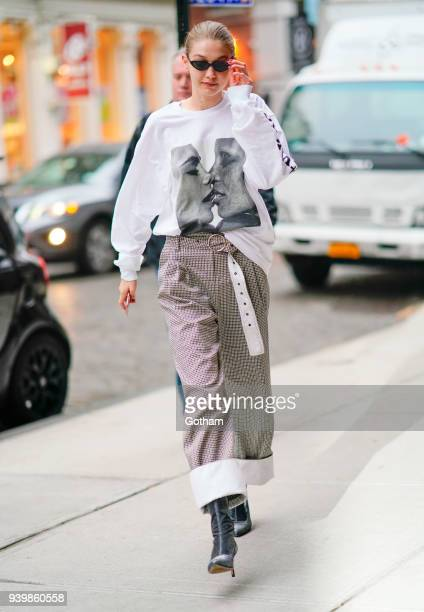 Gigi Hadid wears an oversized shirt with Cara Delevingne and Adwoa Aboah kissing on March 29 2018 in New York City