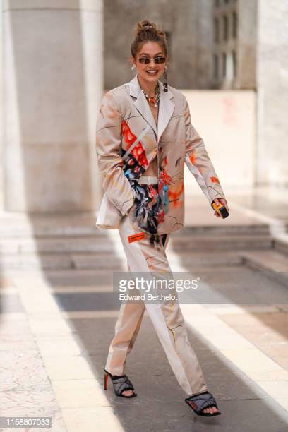 Gigi Hadid wears sunglasses, earrings, necklaces, a Heron Preston lustrous beige pantsuit with colorful paintings print, grey padded heeled mules,...