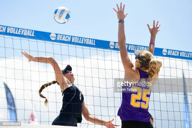 Gigi Hernandez of Pepperdine University spikes the ball past Olivia Powers of Louisiana State University during the Division I Women's Beach...