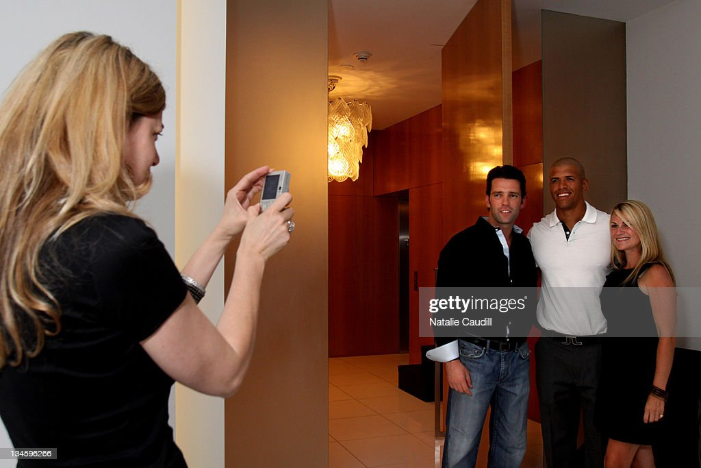 Gigi Howard takes a photo of Kirby Schlegel, Dallas Cowboy Miles Austin and Stephanie Hodges Kennedy at the Vogue and Net-A-Porter.com Spring-Summer 2010 collection preview event at Dallas W Residences on April 22, 2010 in Dallas, Texas.