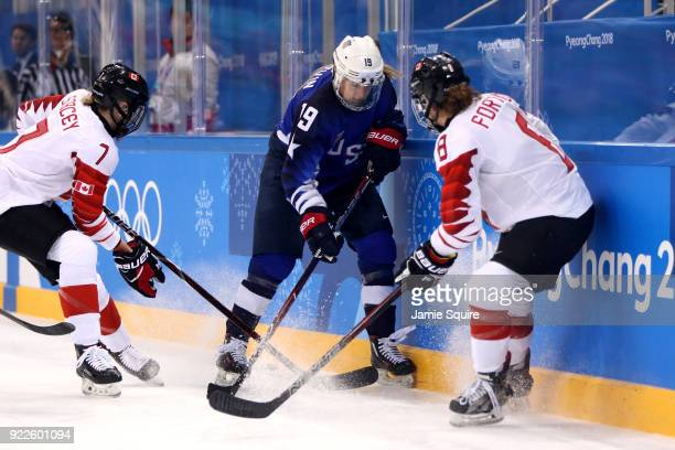 Gigi Marvin of the United States battles for the puck against Laura Fortino and Laura Stacey of Canada in the first period during the Women's Gold...