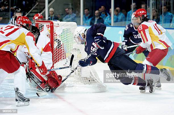 Gigi Marvin of United States takes a shot on goal against Linuo Wang and Yao Shi of China during their women's ice hockey preliminary game at UBC...